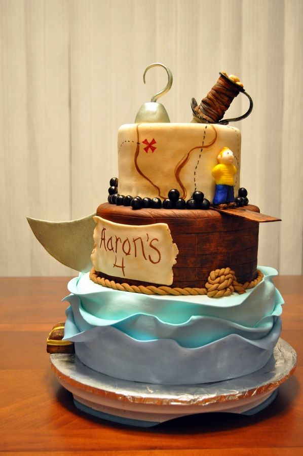 Three tier pirate cake. Everything is edible. I used MMF for everything except the actual hook, plank and sword blade which are gum paste.  Bottom is a ten inch middle is eight and top is six.