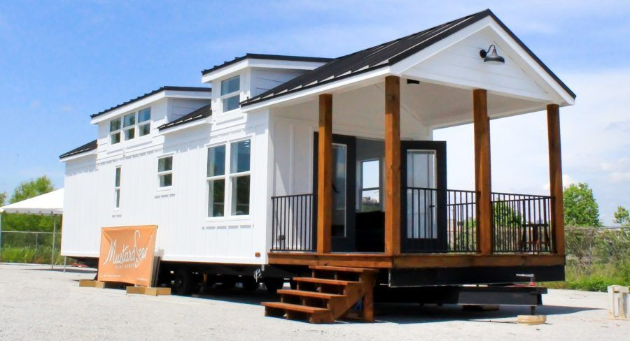 The Zion Park Model Tiny House by Mustard Seed Tiny Homes. Highlights: 520 sf/399 sf on main level, 120 sf loft, 120 sf covered porch; 2 bd/1 ba; Main floor bedroom; Built on a trailer; $95K. Buford, Georgia.