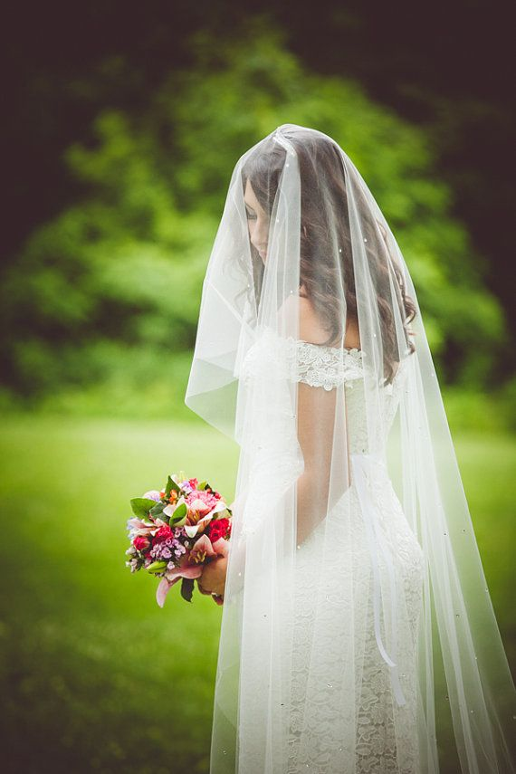 bride wearing long length wedding veil covering her face ...