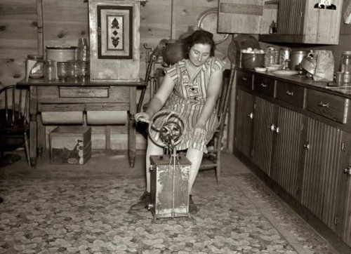 """December 1936. """"Farmer's wife churning butter. Emmet County, Iowa.""""  The Great Depression"""