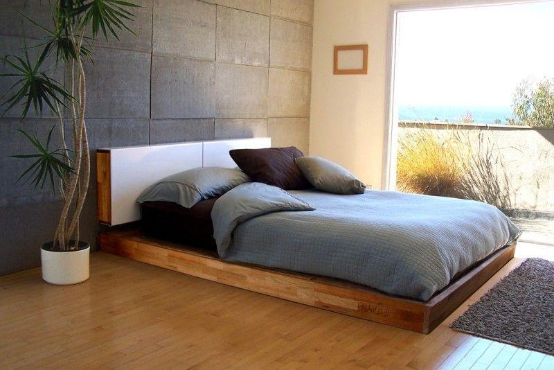 sehr niedriges Bett mit Holzrahmen und Parkettboden im Schlafzimmer