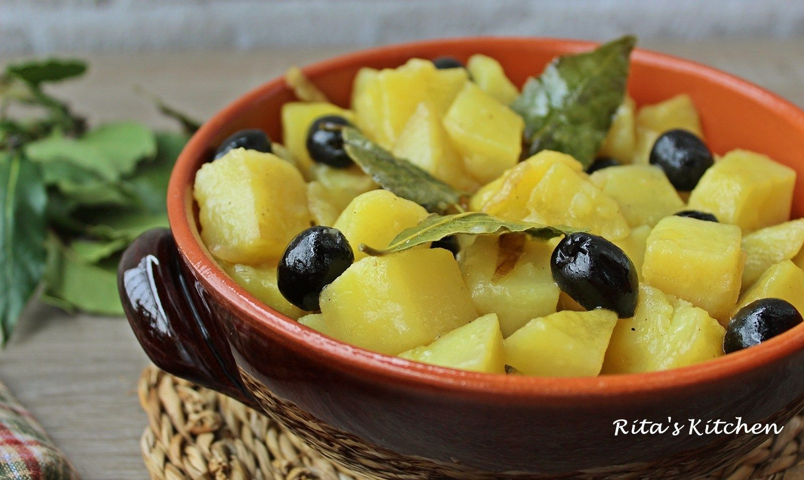 Photo of stewed potatoes with bay leaf and black olives