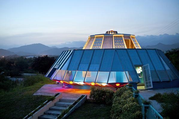 Professor aposentado constrói casa em formato de disco voador usando objetos inusitados. Panelas, bacias e peças de carro formam a estrutura que emite luzes e sons estranhos.