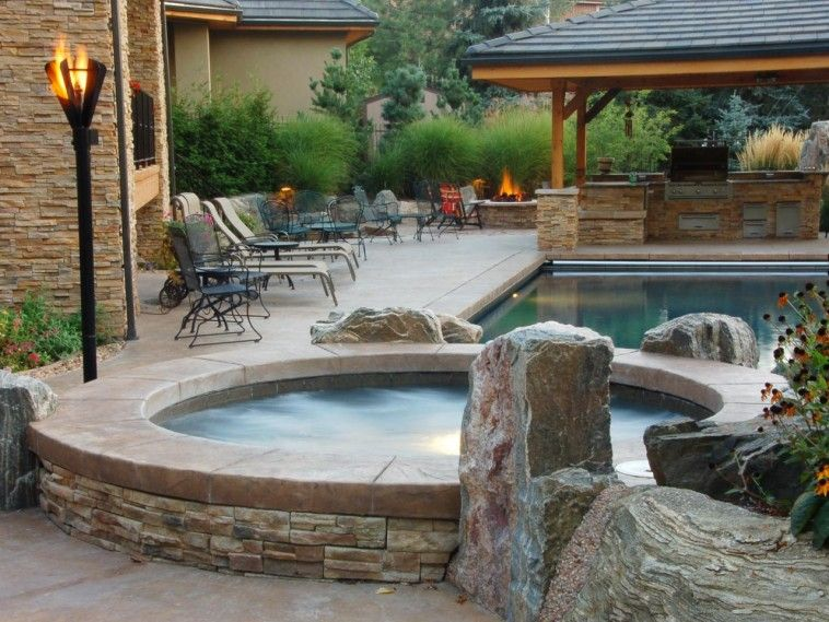 Natural Elements Like Boulders And Tall Gres Provide An Organic Feeling As Well Privacy To A Backyard Hot Tub Flame Lit Torches Are More