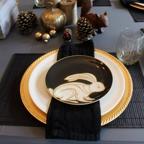 A Christmas/Holiday tablescape in black and gold, with woodland animal plates and accessories