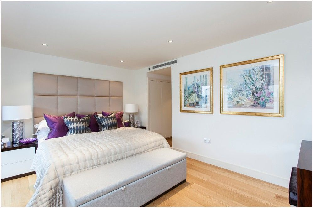 London artwork bedroom bench bedroom ottoman beige bedding beige padded headboard beige wall gold frames metallic table lamp padded headboard purple throw pillow white nightstand