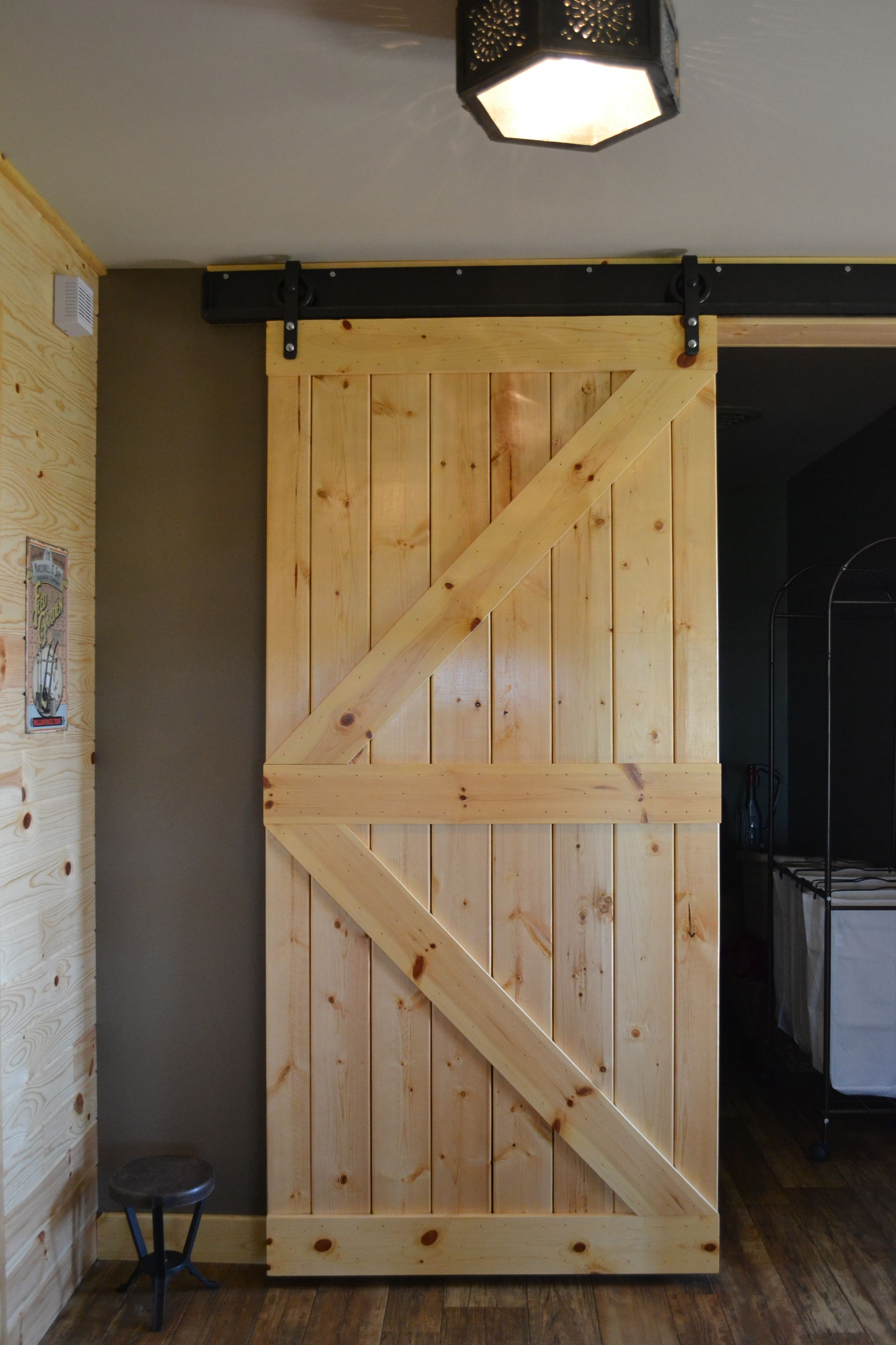Barn Door Created Out Of Our Left Over Knotty Pine Boards The Track Was Fabricated At A Local Welding Diy Barn Door Interior Barn Doors Diy Barn Door Hardware
