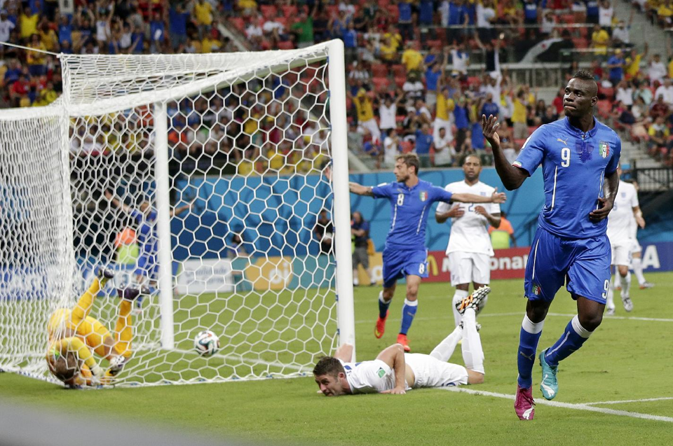 Italy's Mario Balotelli (9) celebrates after getting the ball past England's goalkeeper Joe Hart, left, and Gary Cahill, center, to score his side's... (AP Photo/Marcio Jose Sanchez)