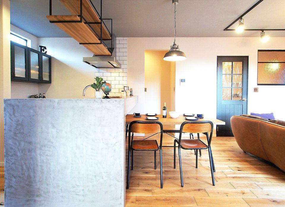モルタルで仕上げたキッチンカウンターとアイアンを取り入れた家具が