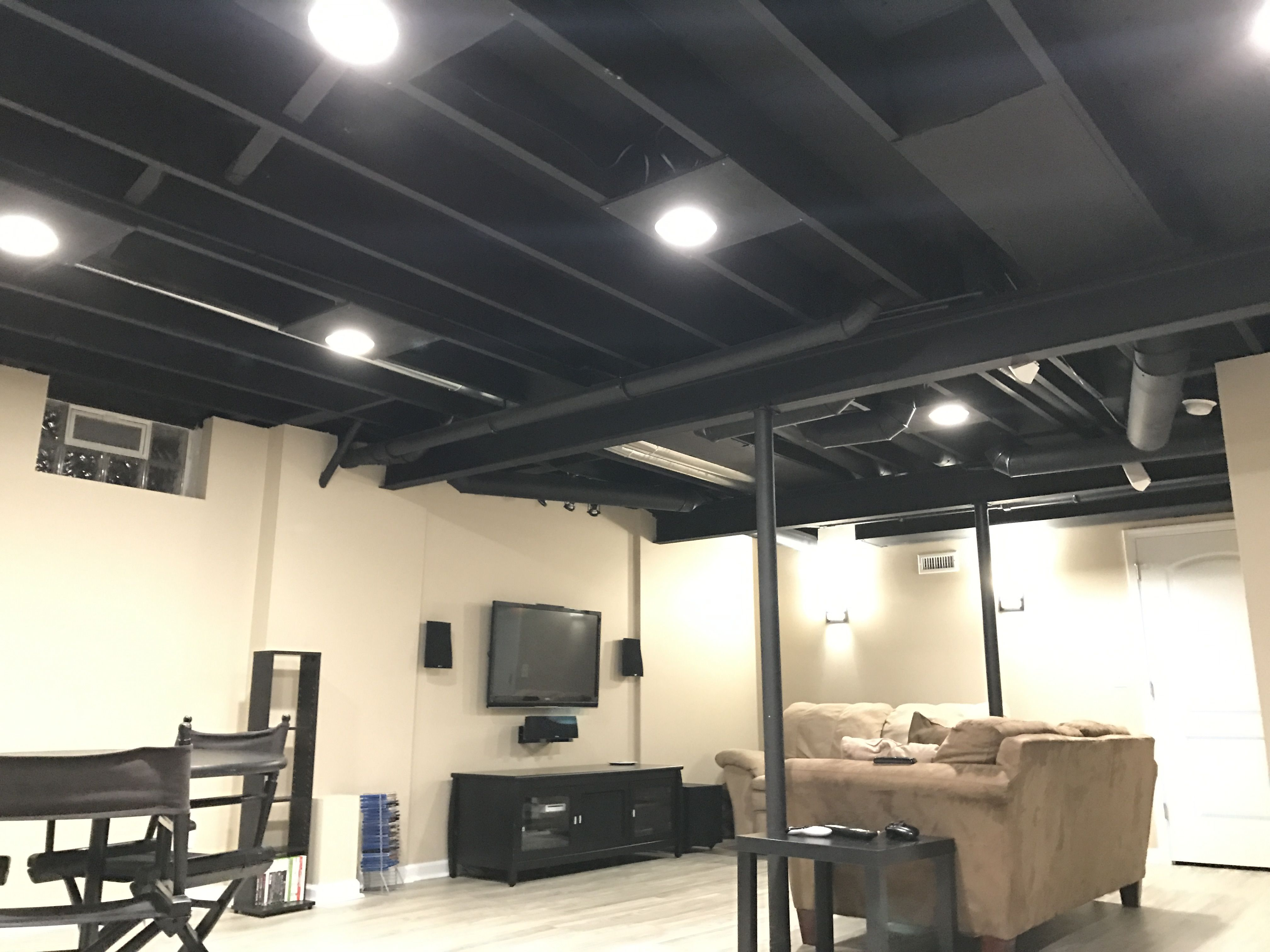 Exposed basement ceiling painted black. Plywood added