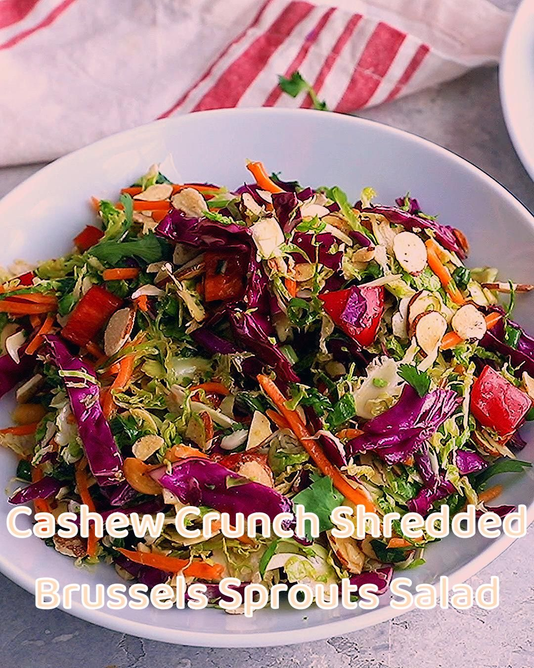 Delicious cashew crunch shredded brussels sprouts salad tossed in a flavorful sesame ginger dressing. This easy vegan salad recipe is loaded with colorful veggies and topped with crunchy roasted cashews and toasted almonds. Great for meal prep, parties and potlucks! #saladrecipe #vegetarian #mealprep #potluck