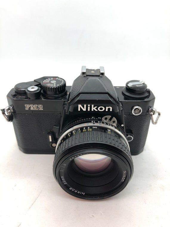 Nikon FM2 BLACK Body 35mm Camera w/ Nikkor 50mm f/1.8 Lens! Camera is in great condition with a few signs of use. Optics are fantastic. Rare black body! All of my cameras and lenses have been fully tested. Any cameras or lenses that have any issues when I acquire them have been professionally repaired before listing them on Etsy, and all have a 30 day warranty.  If the camera needs repairs other than damage from buyer, I pay all shipping charges back to my location and will repair or replace the