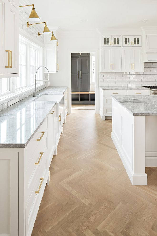 White cabinets gold fixtures and hardware herringbone wood floor