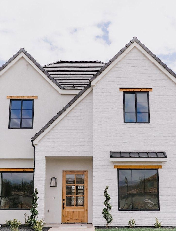 White painted brick exterior with black windows and wood - How much to stucco exterior of house ...