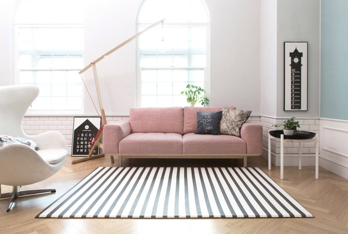Beautiful, minimal, modern, scandinavian style living room with pastel pink sofa, black and white striped rug, wooden floorboards, white armchair and pastel blue feature wall. Carpets & rugs by 아날로그라이프