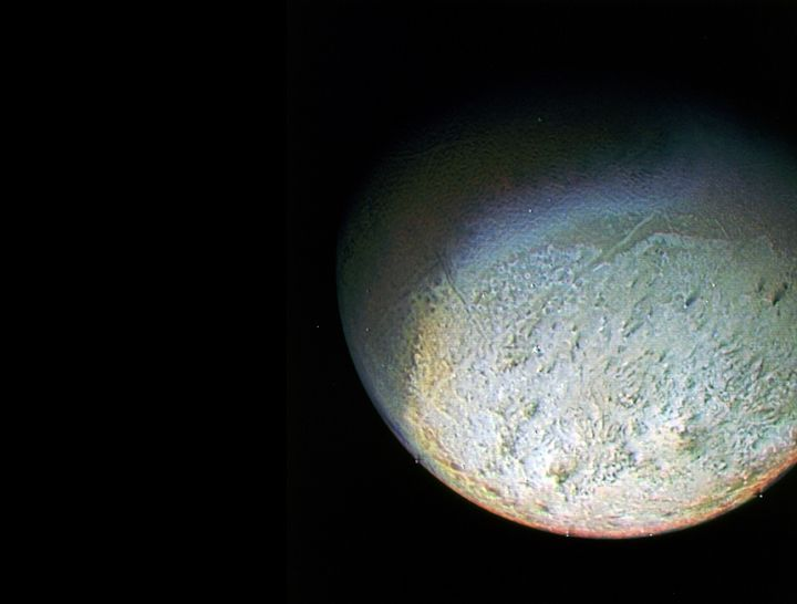Neptune's large satellite Triton is one of the coolest objects in our solar system. It is so cold that most of Triton's nitrogen is condensed as frost, giving its surface an icy sheen that reflects 70 percent of the sunlight that hits it.