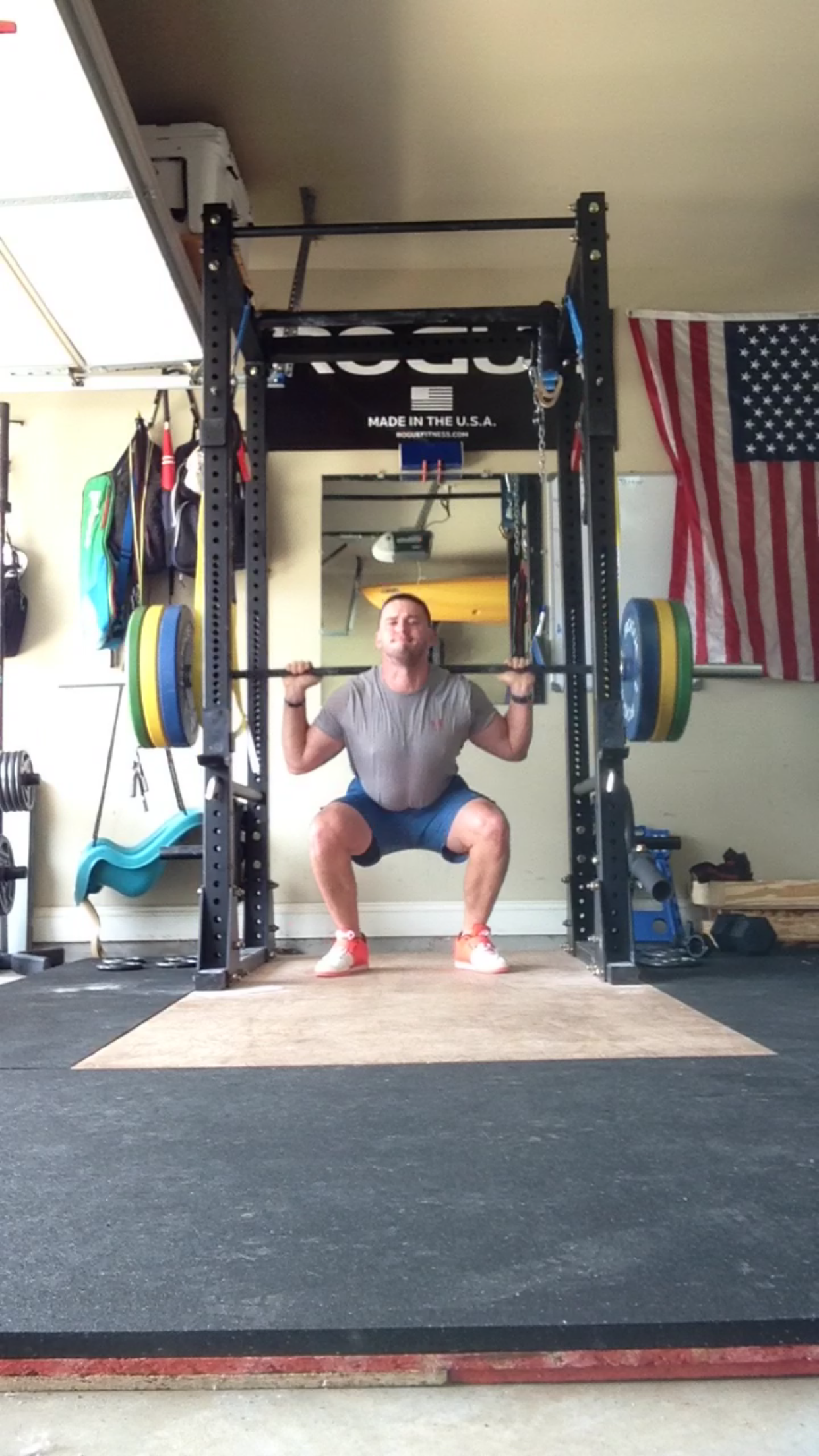 Rogue equipped garage gym with diy lifting platform plus a baby