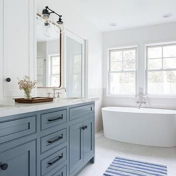 blue dual sink vanity with light gray herringbone floor