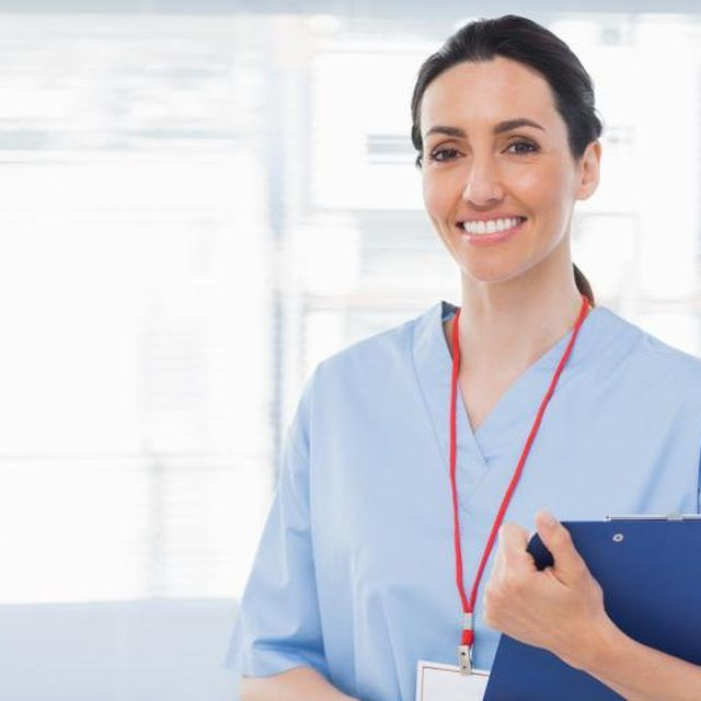 A nurse smiling in her office.