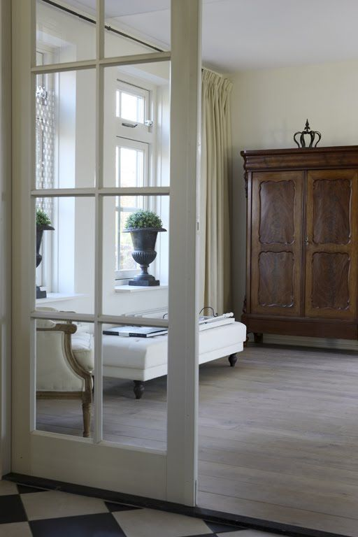 use a french door/window panel to add interest to a standard boxy side room. + light wood flooring