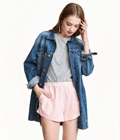Lys rosa. En kort shorts i vevd, elastisk kvalitet. Den har bred elastikk i midjen. Sidelommer.