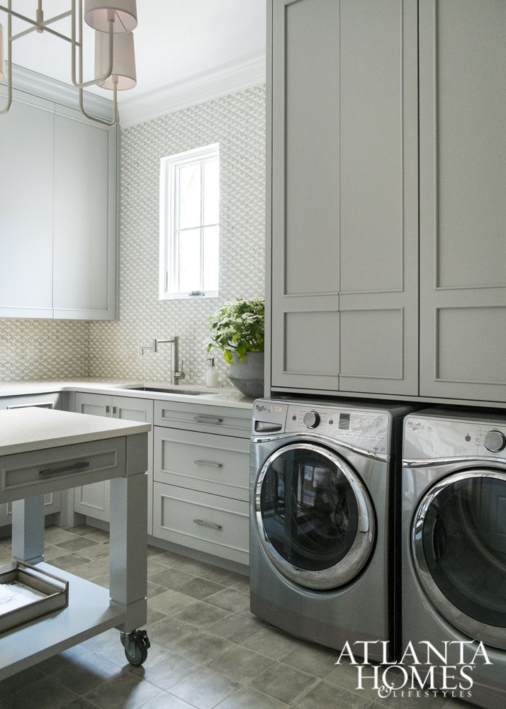 The mix of textures and shapes continues into the laundry and bath, where Ferguson incorporated softer elements such as a custom gray-stained mahogany vanity, heathered gray linens and a cream vanity stool.