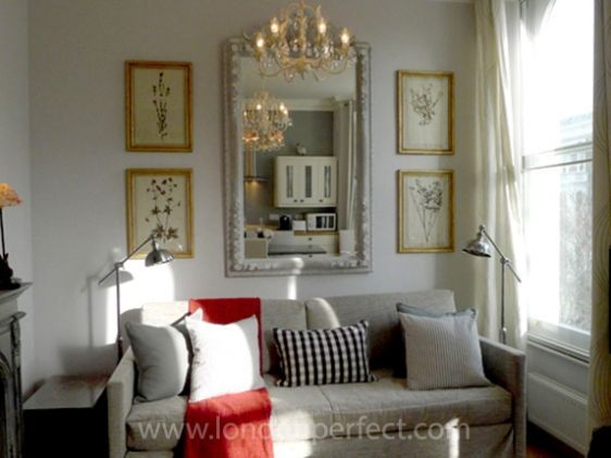 Large Vertical Mirror Centered Over Couch With Frames On Both Sides. Part 68