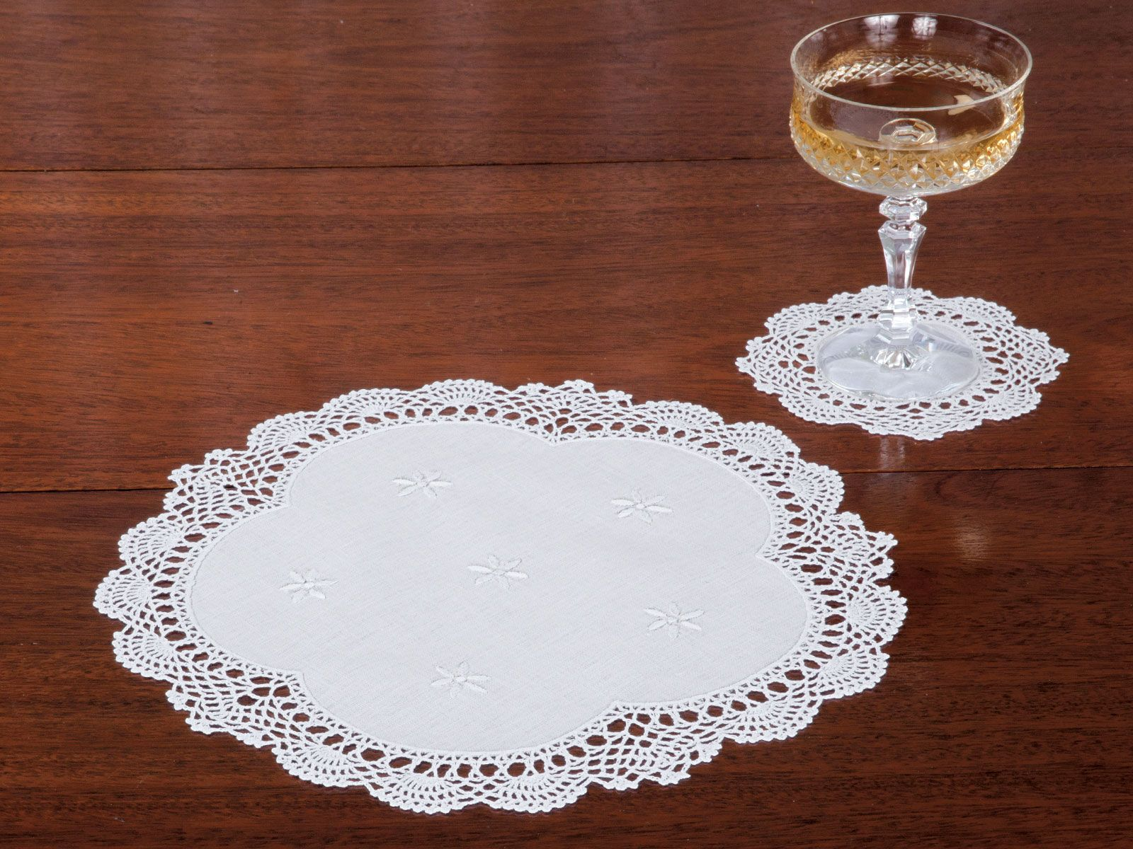 Queen Anne Doilies. Recalling the refinements of days long gone by, these fine Italian linen doilies are made to be enjoyed today and treasured tomorrow. Exquisitely crafted with scalloped hand-crocheted borders and hand-embroidered daisies in the center, they turn any place you put them into a thing of beauty. Imported in White in a full range of sizes.  #TableLinen #Doily #schweitzerlinen