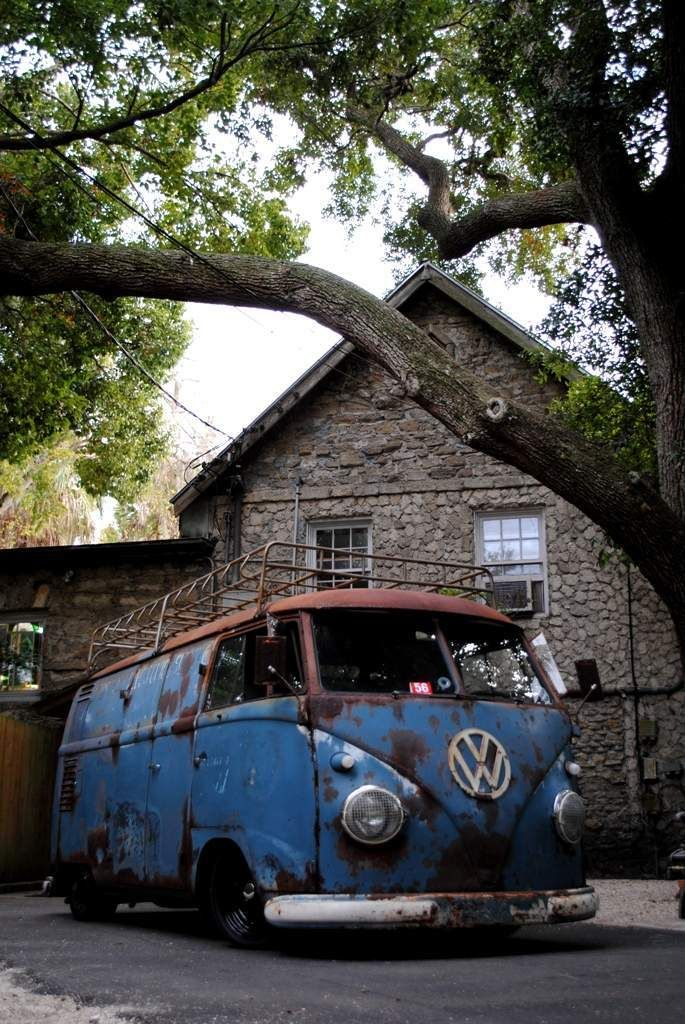 Blue VW Bus in front of rock house