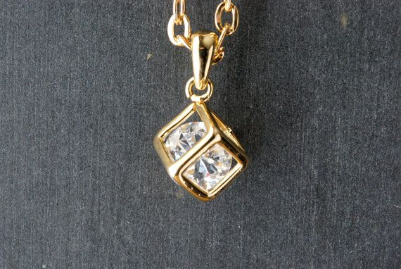 This little gold plated open cube pendant features a single, small,  gem. Suspended from matte gold tone cable chain and finished