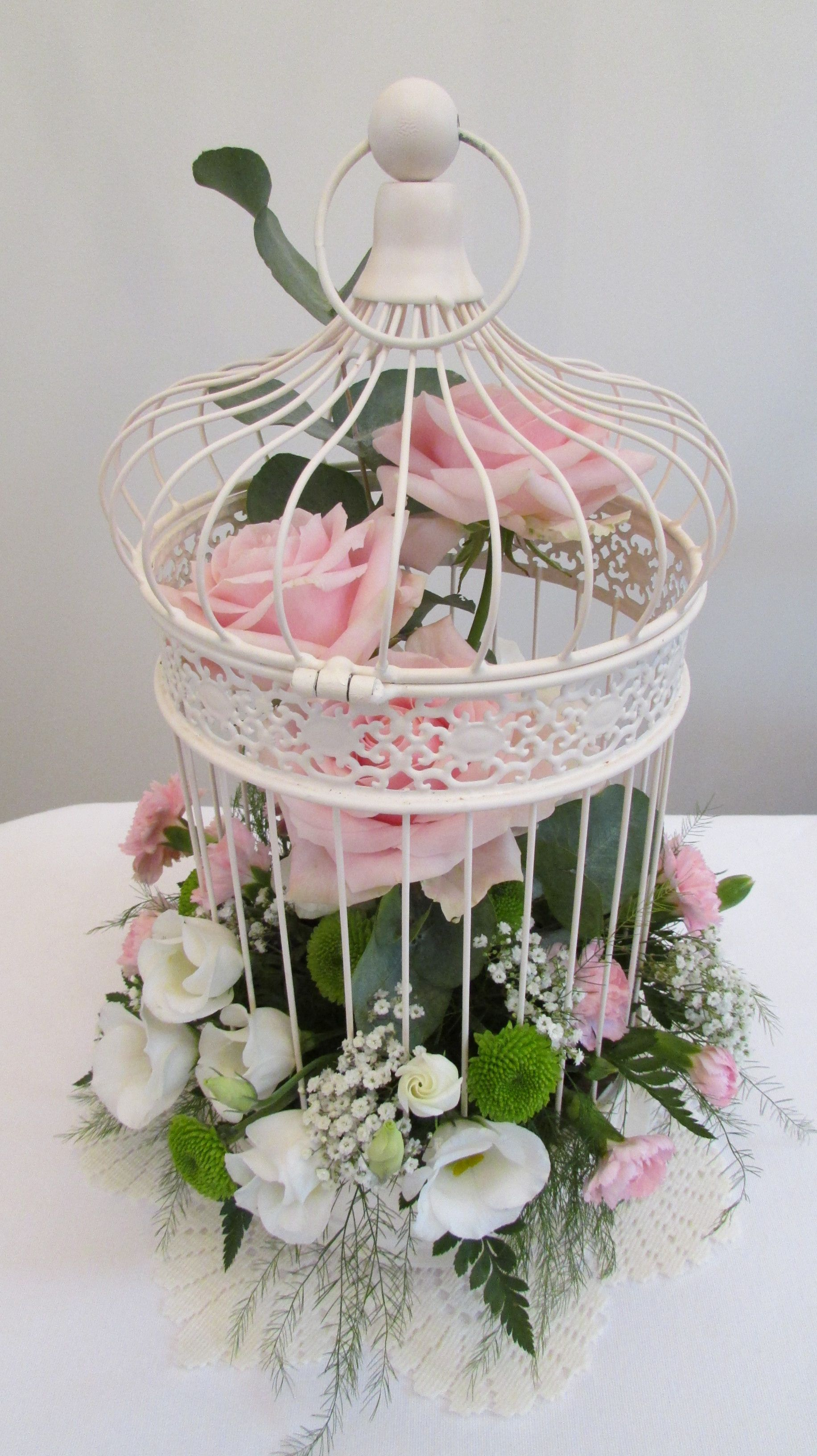 Vintage bird cage decorated with fresh flowers in pinks By Best