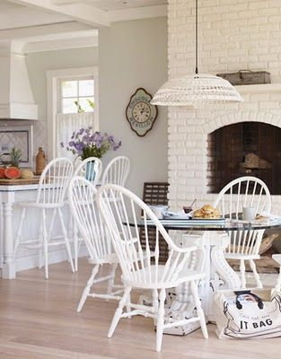 Painted fireplace & old farm-style chairs create a beautiful country-style kitchen.  I love this!