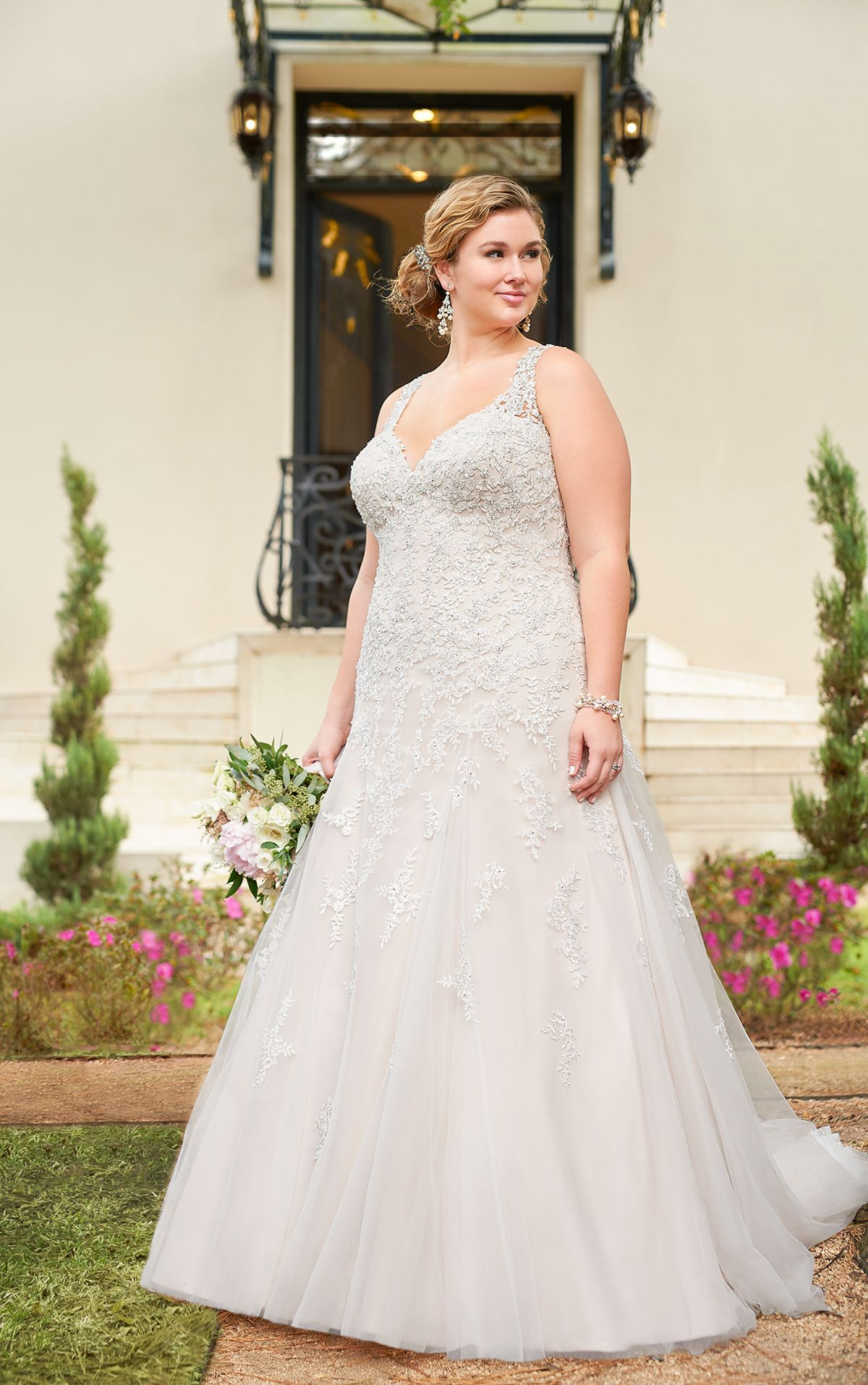 This sparkling silver lace plus size wedding dress from Stella York is sure to be a show-stopper! The modern modified A-line silhouette boasts metallic lace that flows down from the Diamante covered bodice onto a light-as-air tulle skirt. The sweetheart neckline and illusion lace straps create an organic-edge neck that will flatter any bride-to-be! Sparkling crystal bead work brings attention to the bride's face while the tulle skirt adds drama and dimension to the look.
