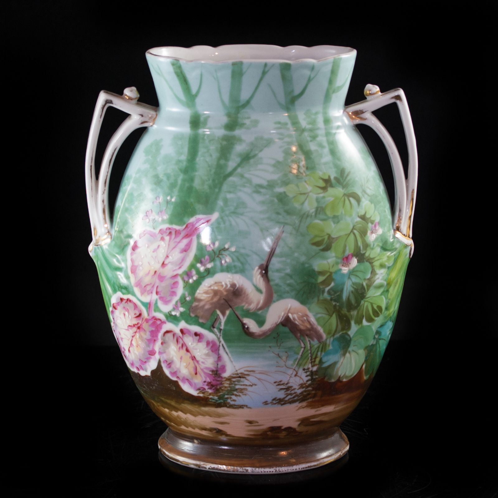Lot #34: Old Paris Vase DESCRIPTION: An old paris porcelain vase with a hand painted illustration of two cranes in the wild. The colors used in the illustration match the famille rose color pallete and the handles of the vase are also decorated with gilded patterns running along its sides.  CIRCA: 20th Ct. ORIGIN: France DIMENSIONS: 5 1/2″ W x 10 3/4″ L x 13 3/4″ H