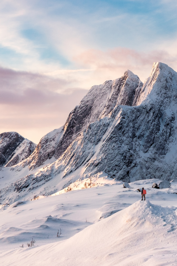 Beautiful winter scenery in Norway. Snow-capped Norwegian mountain with a hiker looking on