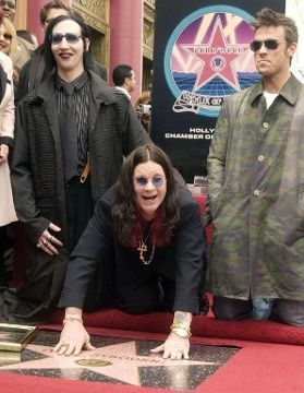 Osbourne, flanked by Marilyn Manson and Robbie Williams, touches his star after he was honored with the 2,195th star on the Hollywood Walk o...