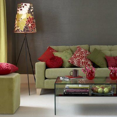 Green and red furniture and accessories provide colourful accents in this living room. The bold print shade ties into the scheme, repeating its colours and cushions. The dark grey walls and white flooring creates a soft and subtle backdrop