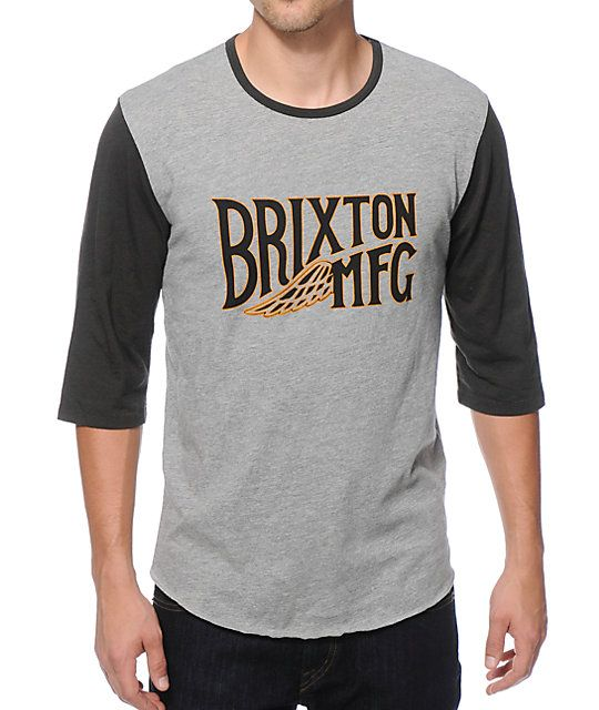 0334cc989822 Sport some clean two tone style with black 3/4 length raglan sleeves on a  charcoal body with a black and yellow Brixton MFG wing logo graphic at the  chest.