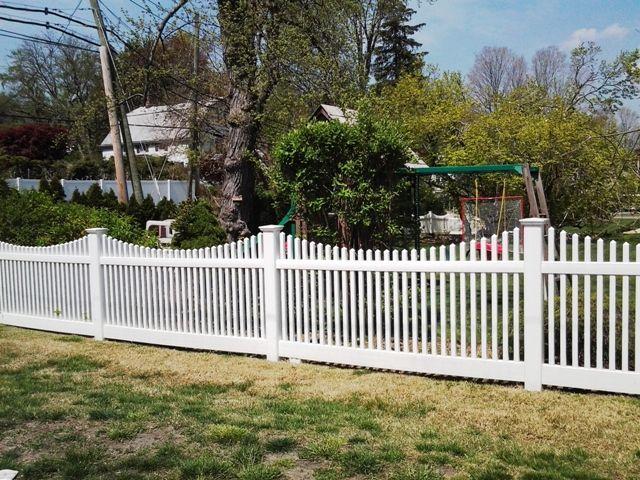 Scalloped white vinyl picket fence