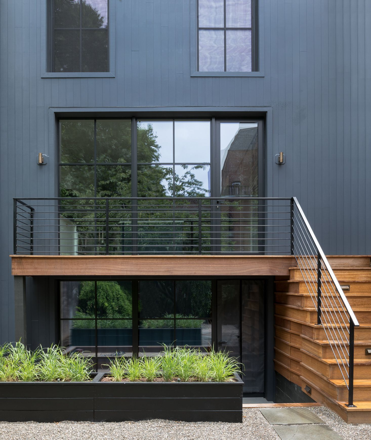 Modern exterior of historic Jersey City row house with mahogany deck.