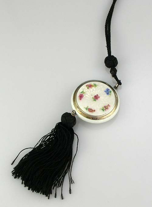 "Sterling Silver Guilloche Enamel Compact Circa 1920     A sterling silver guilloche enamel white compact with hand painted flowers on the top of the lid. The interior has mirror and puff. Original black tassel and rope handle.     Diameter: 2""    Price: $295.00"
