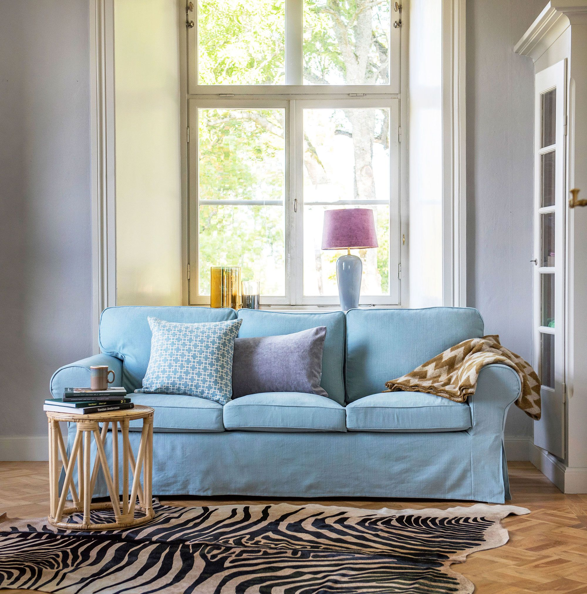 Baby blue light blue sofa with a faux zebra skin rug