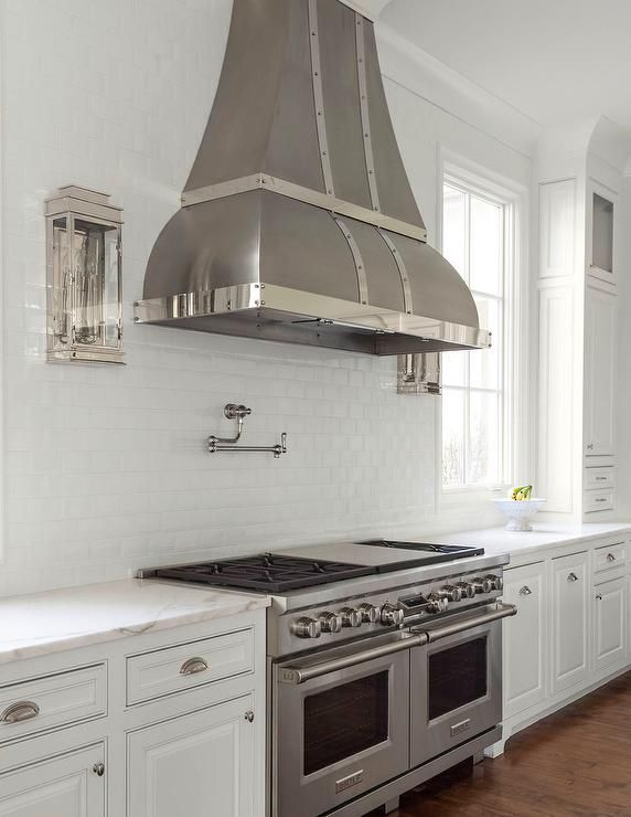 A Dark Steel Vent Hood Is Mounted On A White Beveled Subway Tile Backsplash Between Nickel And Glass Kitchen Hoods Kitchen Range Hood White Beveled Subway Tile
