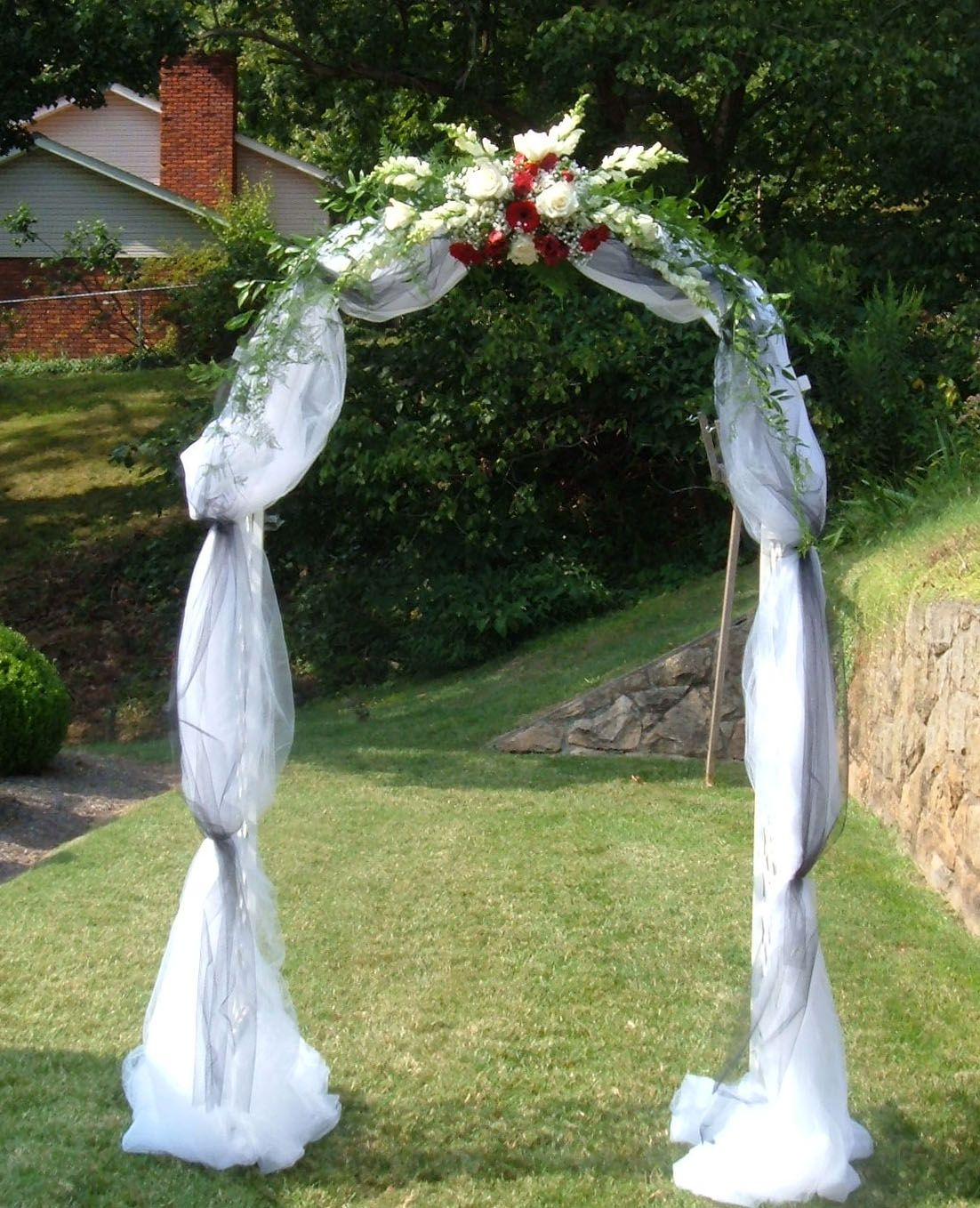 Wedding arch covered with tulle and accented with flowers for Arch decoration supplies