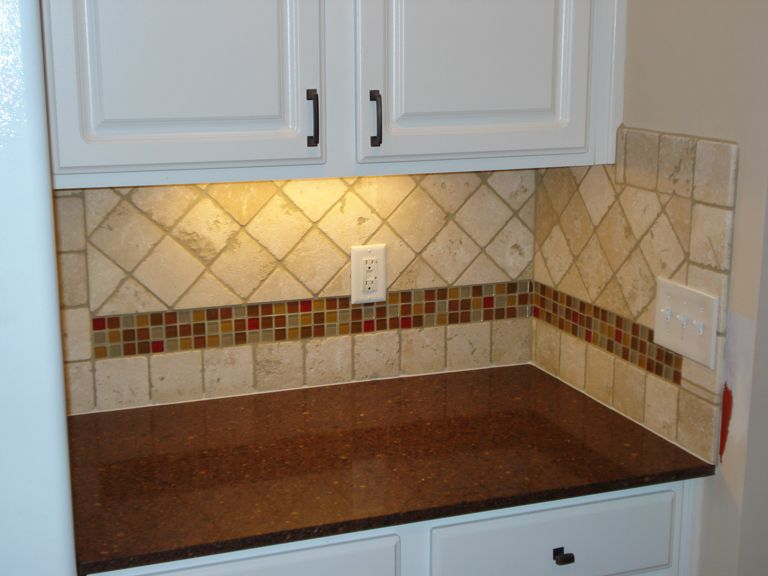 tumbled marble backsplash with multi-colored glass accent strip