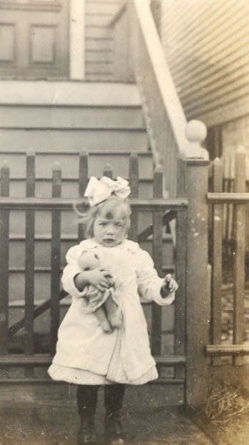 Antique photograph of a child holding her Kewpie.