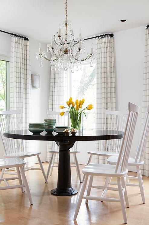 contemporary country dining room features a round black dining