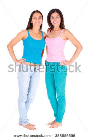 Two smile best girlfriends posing in studio, wearing summer style outfit t-short and jeans. Girls smiling and having fun. Isolated on white
