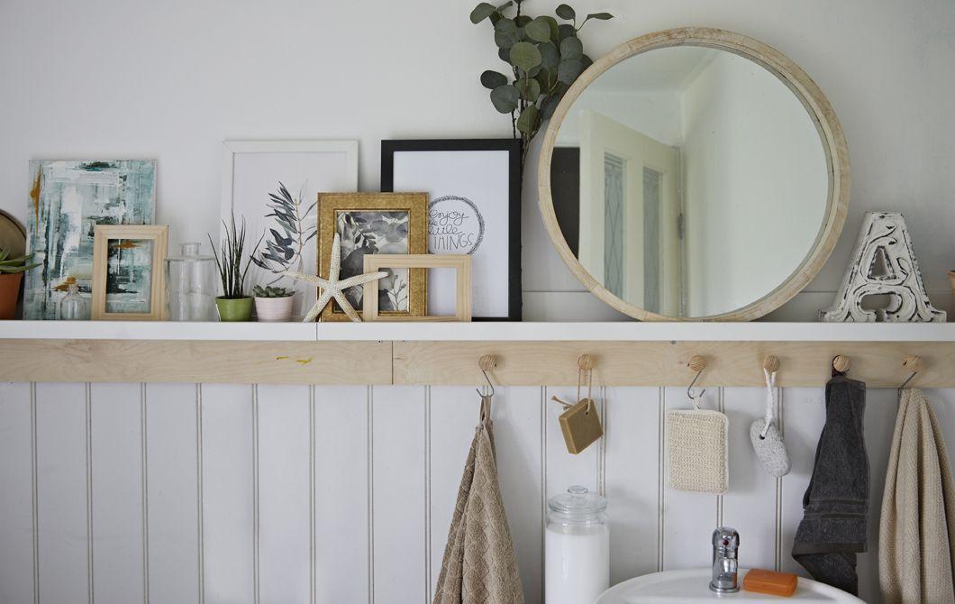 Un bagno con specchio alcune piante quadri e conchiglie su uno