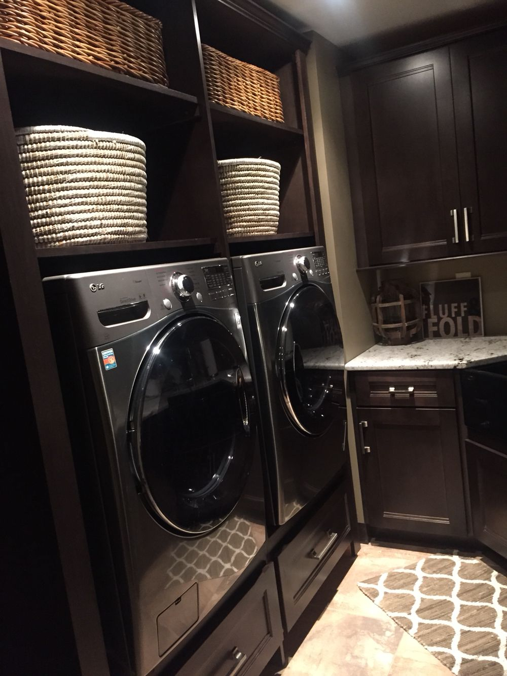 Laundry Room. Built In Cabinet Design. Side By Side Washer And Dryer Raised  Up On Top Of Cabinets, Enclosed. Dark Cabinets. Stainless Steel Appliances.